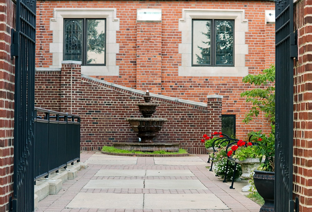 Courtyard fountain with wrought iron black benches along the walkway with red geranium planters