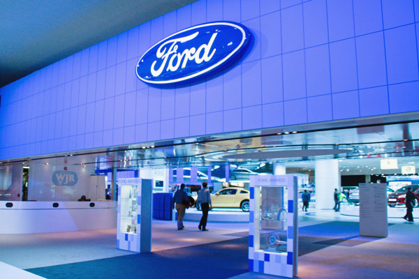two men walking through the blue Ford display.