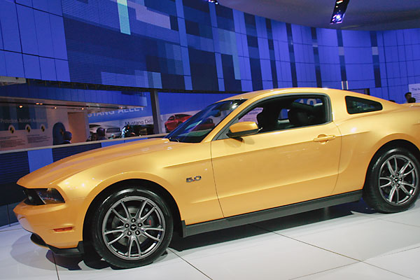 gold two-door Ford Mustang.