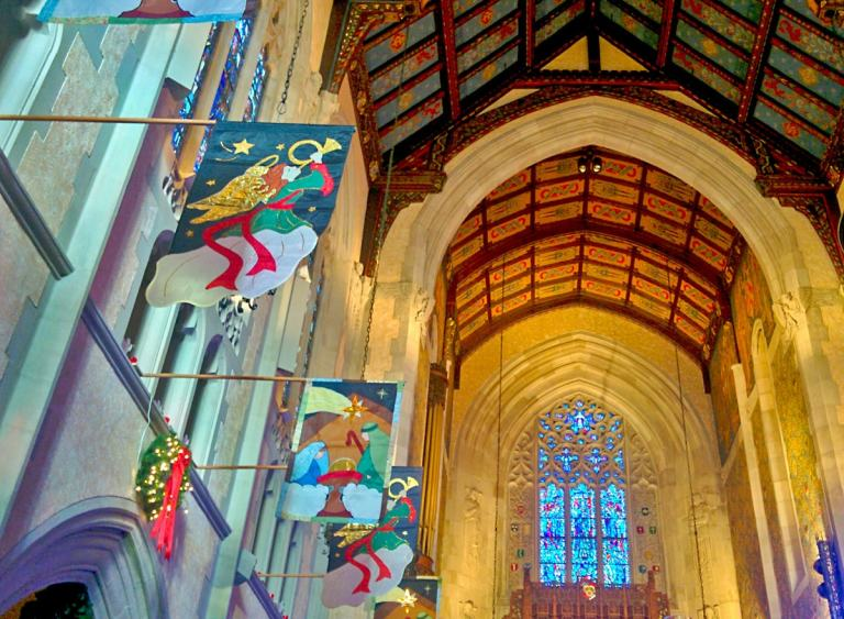 Beautiful stained glass window, arched ceiling, and Christmas banners hanging from the balcony