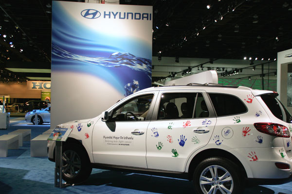 White Hyandai Hope on Wheels SUV covered with children's colorful handprints