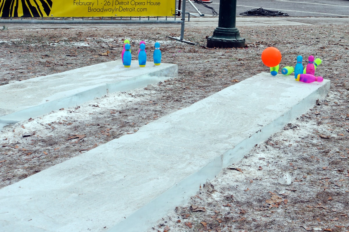 an orange ball knocks down bowling pins on the ice bowling alley at the ice festival