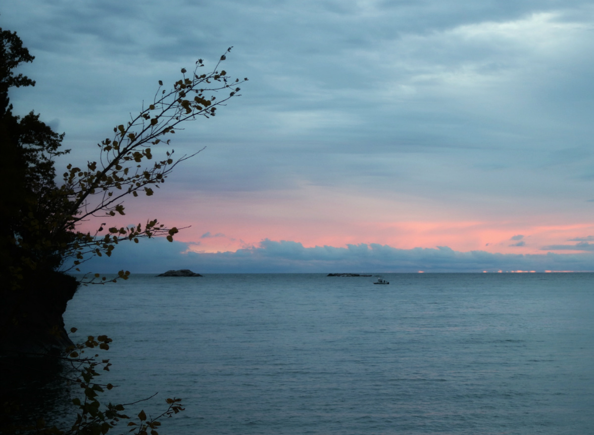 a boat slowly travels on Lake Superior with the pink clouds of dawn in the background