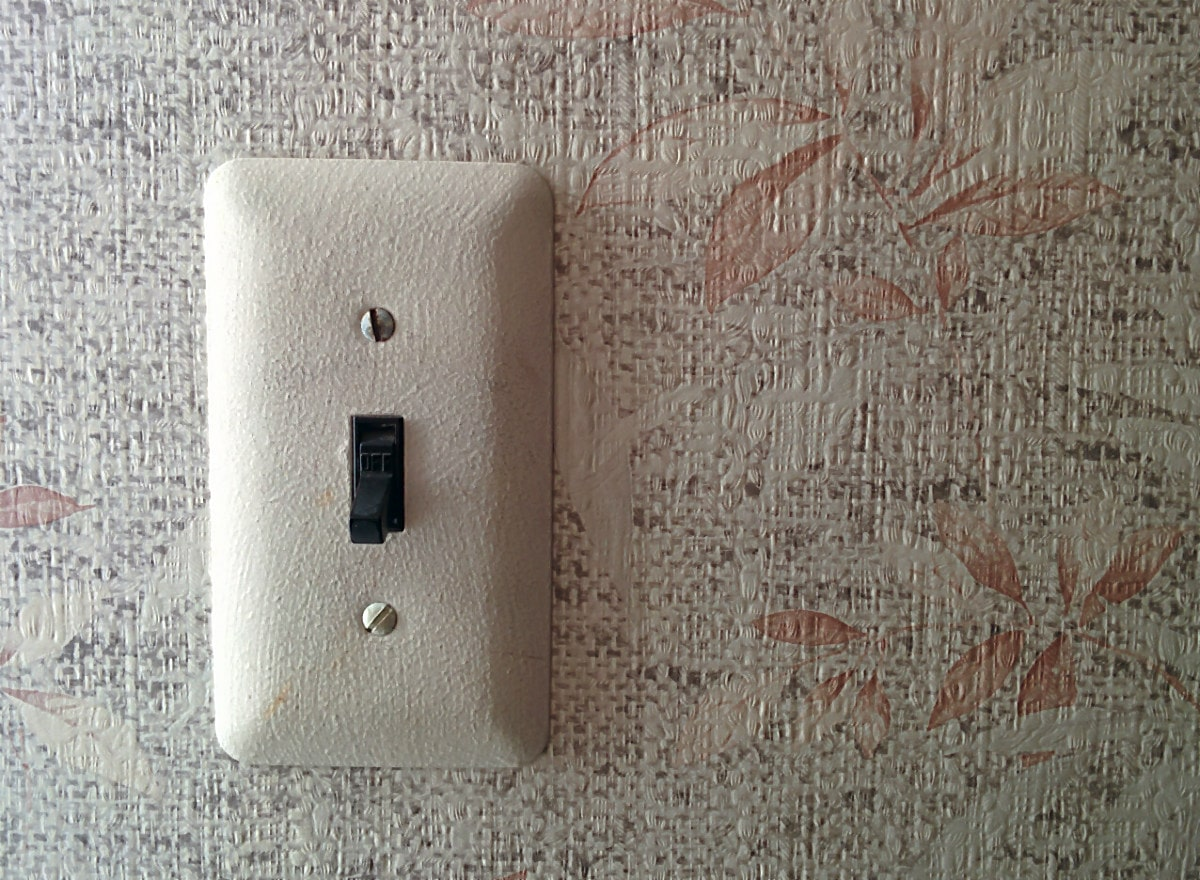 single light switch on a brown and beige wallpapered wall.