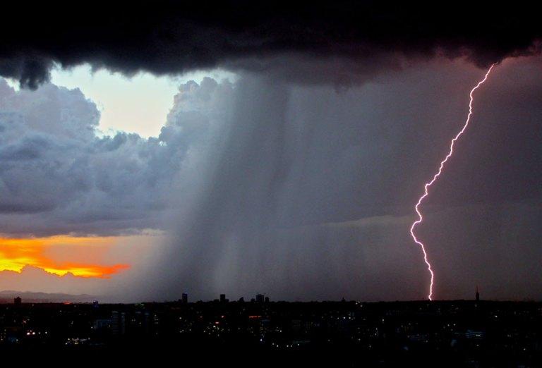 lightning lights up the stormy sky over the city