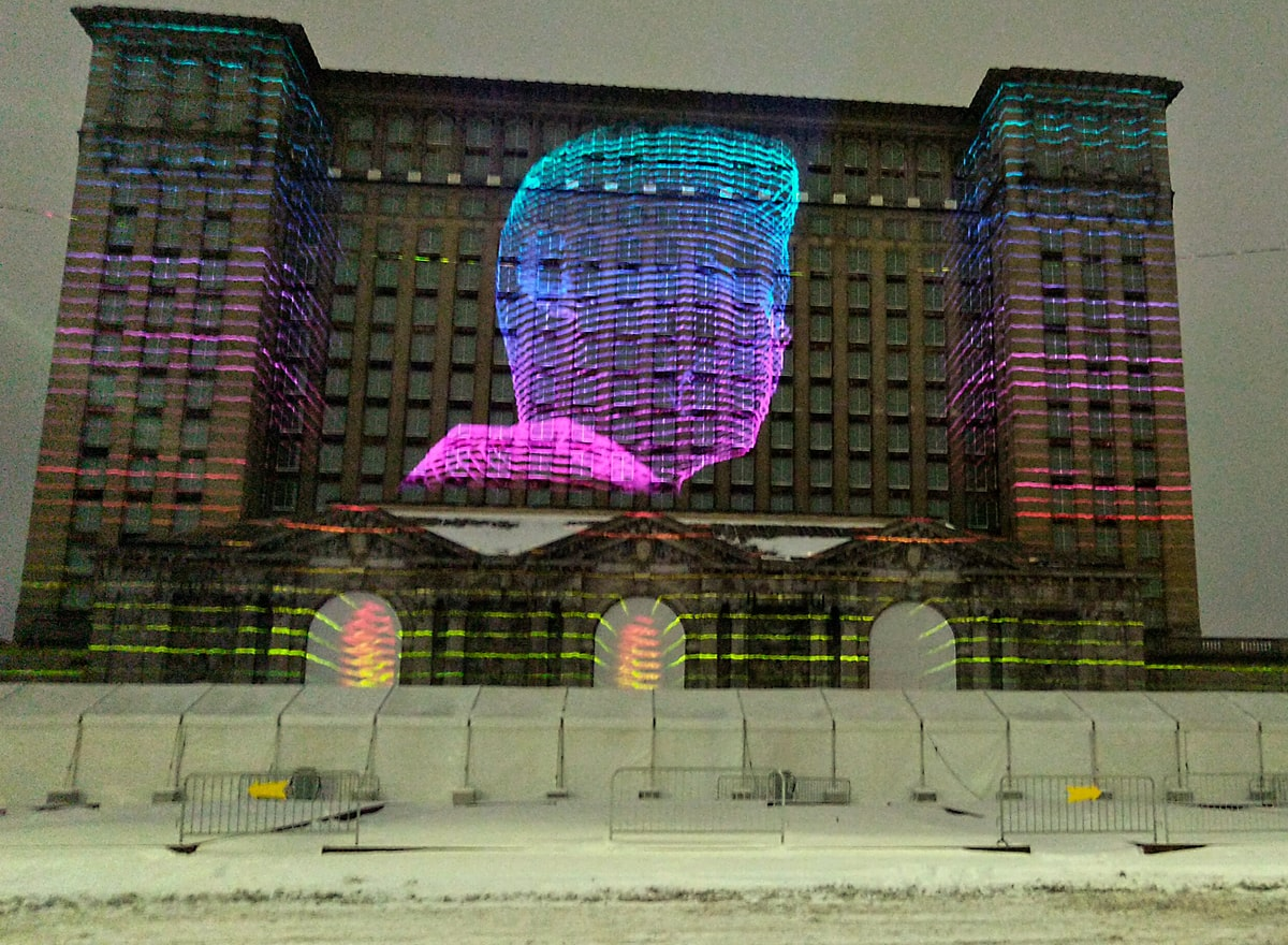 blue and purple gradient colored illustration of a person's profile lights up the front of the old Michigan Central Station train station.