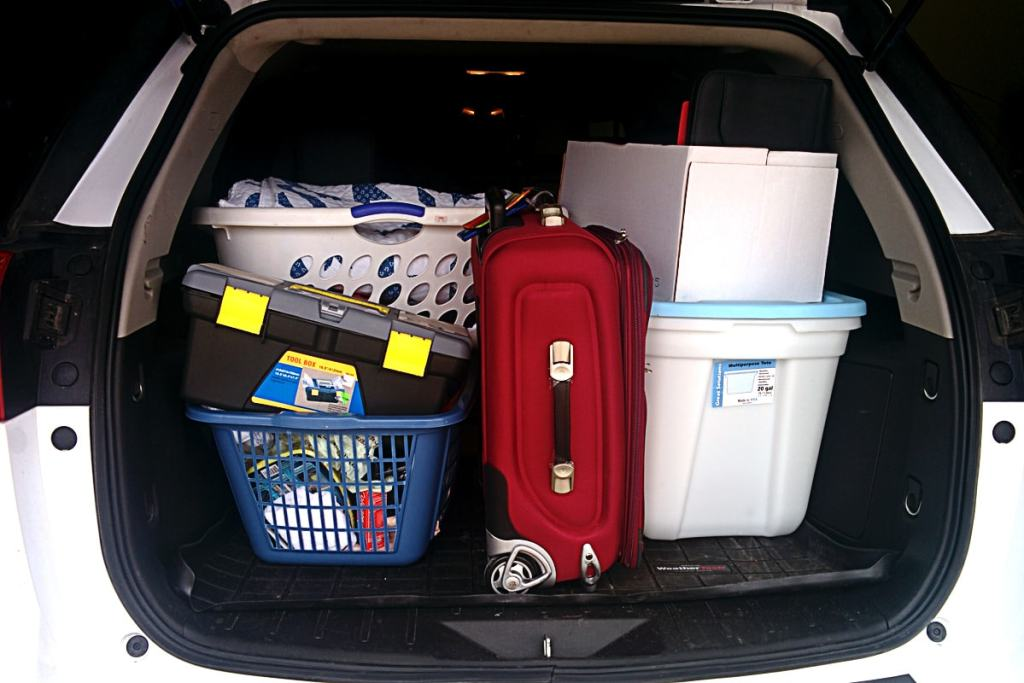 Red suitcase, moving boxes, and toolbox fill the trunk of a vehicle