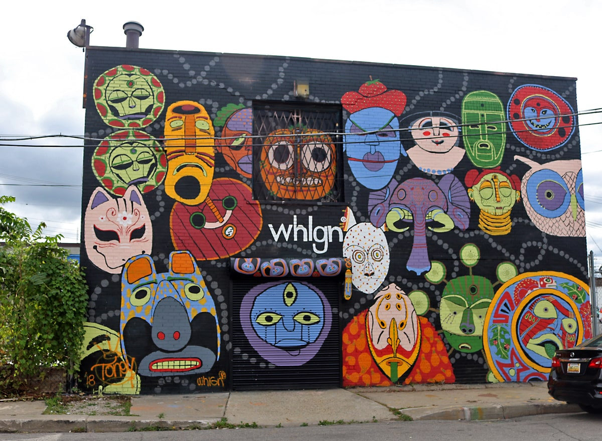 colorful blue, green, orange, and pink abstract masks of people and animals stand out against a black wall on Orleans Street