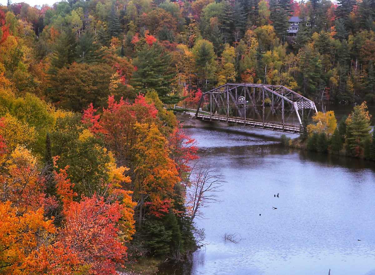 truss bridge crossing a river with brilliantly colored trees in fall colors of gold, red, and orange