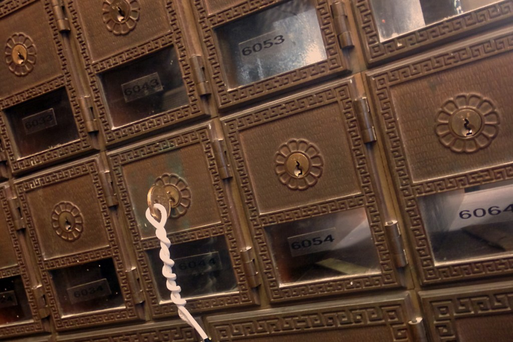 old-fashioned mail boxes at the post office, one box with a key in it