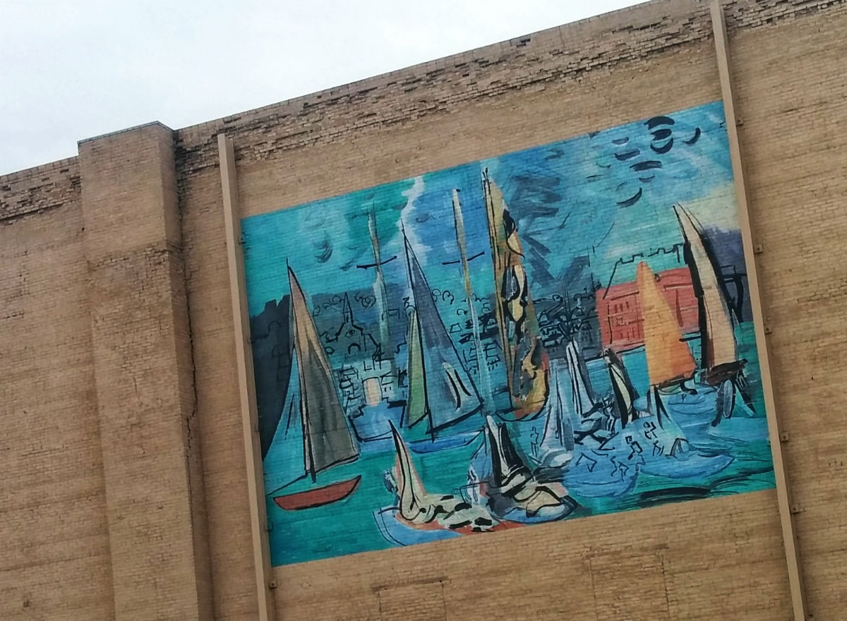 modernistic mural of blue and gold sailboats on a green-blue water