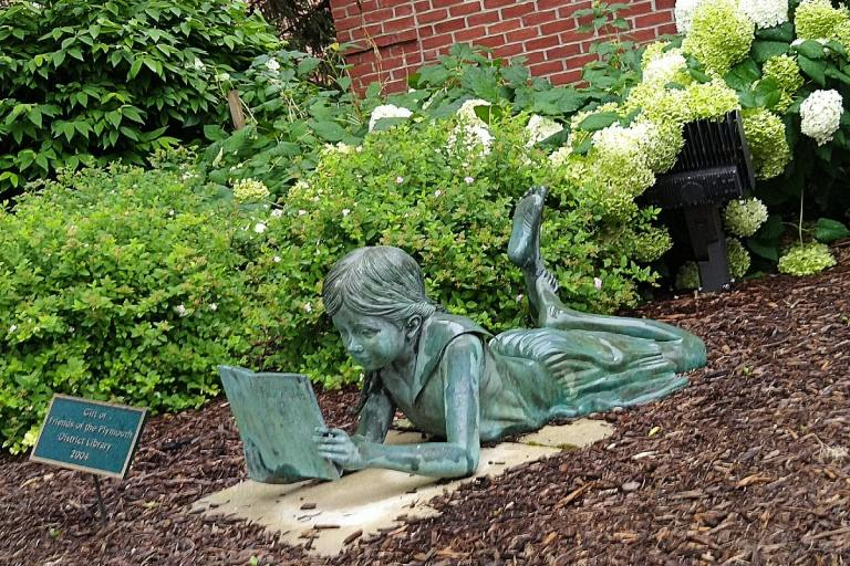 Green-colored sculpture of girl laying down reading a book, brown mulch surround the sculpture, green-leafed shrubs in the background.