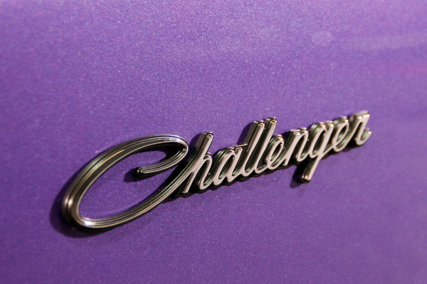 silver Dodge Challenger logo on purple car