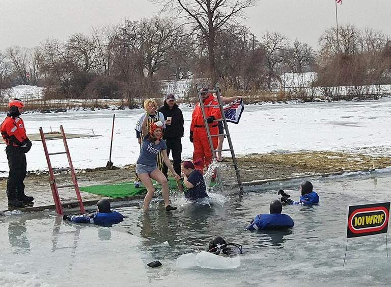 woman midway in air as she jumps into the icy water, Detroit Police and U.S. Coast Guard in the water ready to help.