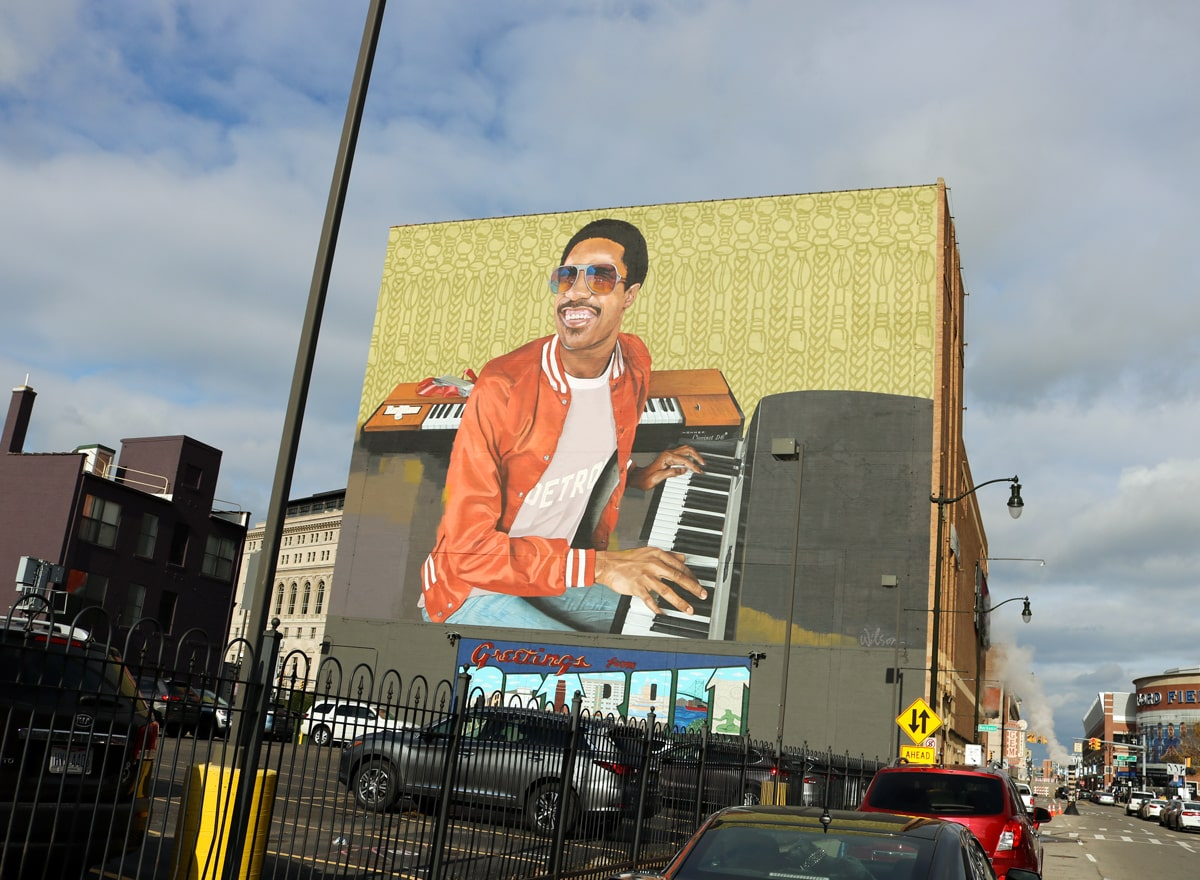 On the side of a building, a young-looking Stevie Wonder in an orange jacket smiles as he plays piano.