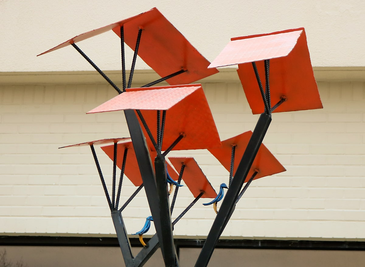 steel sculpture with orange rooftops sheltering bluebirds.