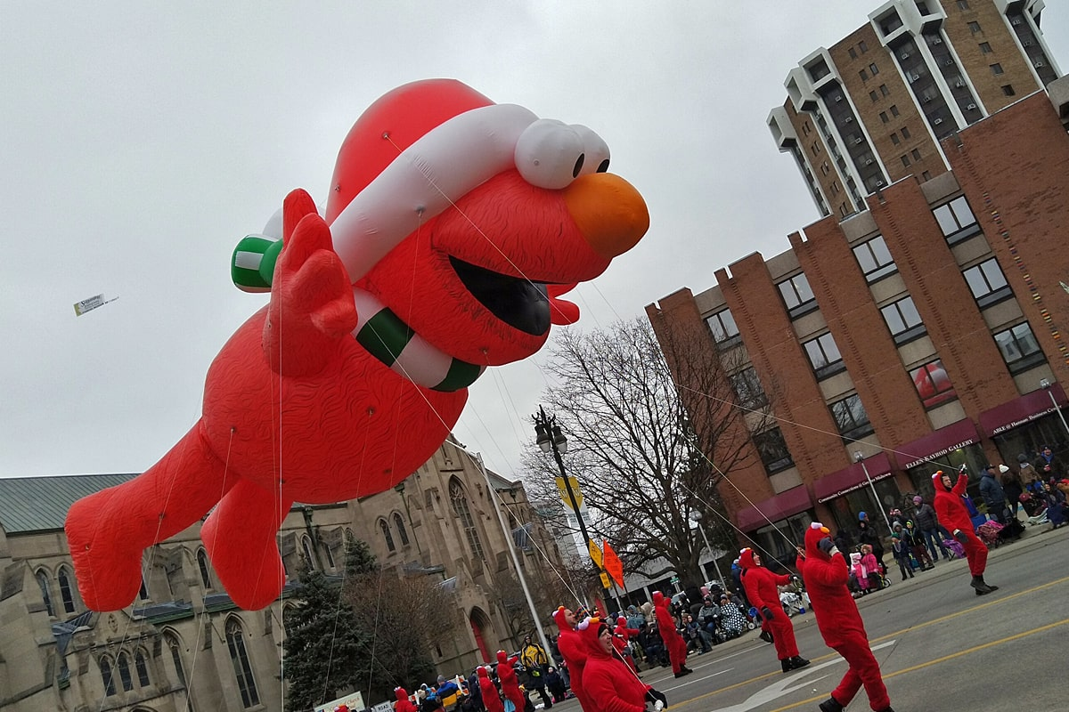 Bright red Elmo balloon wearing a white-trimmed hat, travels down the parade route, with a troop of red-costumed handlers holding him close to the ground.