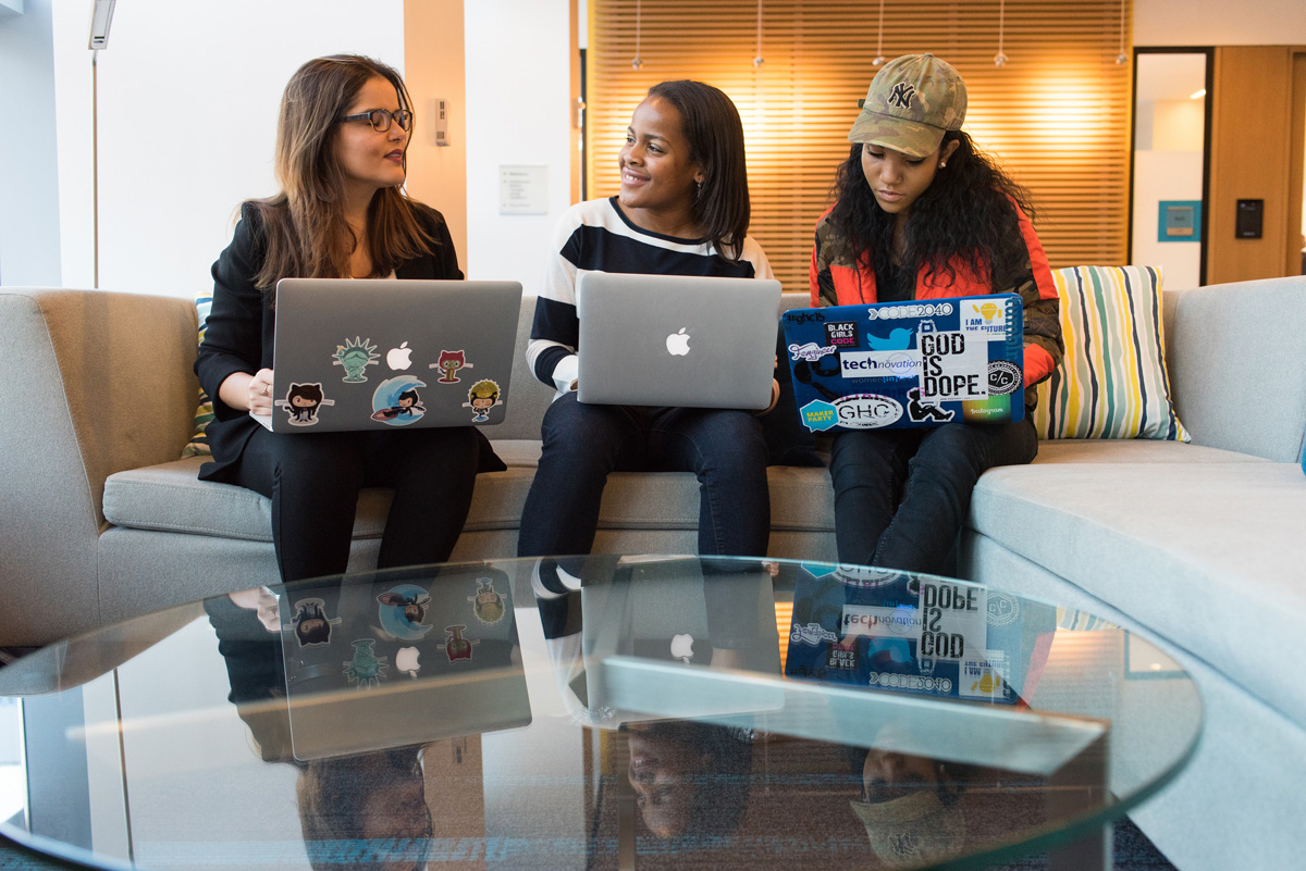 three women talking with laptops on their laps while sitting on the couch