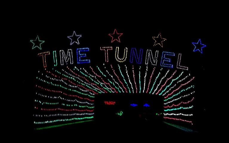 multicolored lights over the highway display stars with the word Time Tunnel over arching red and green lights forming a tunnel.