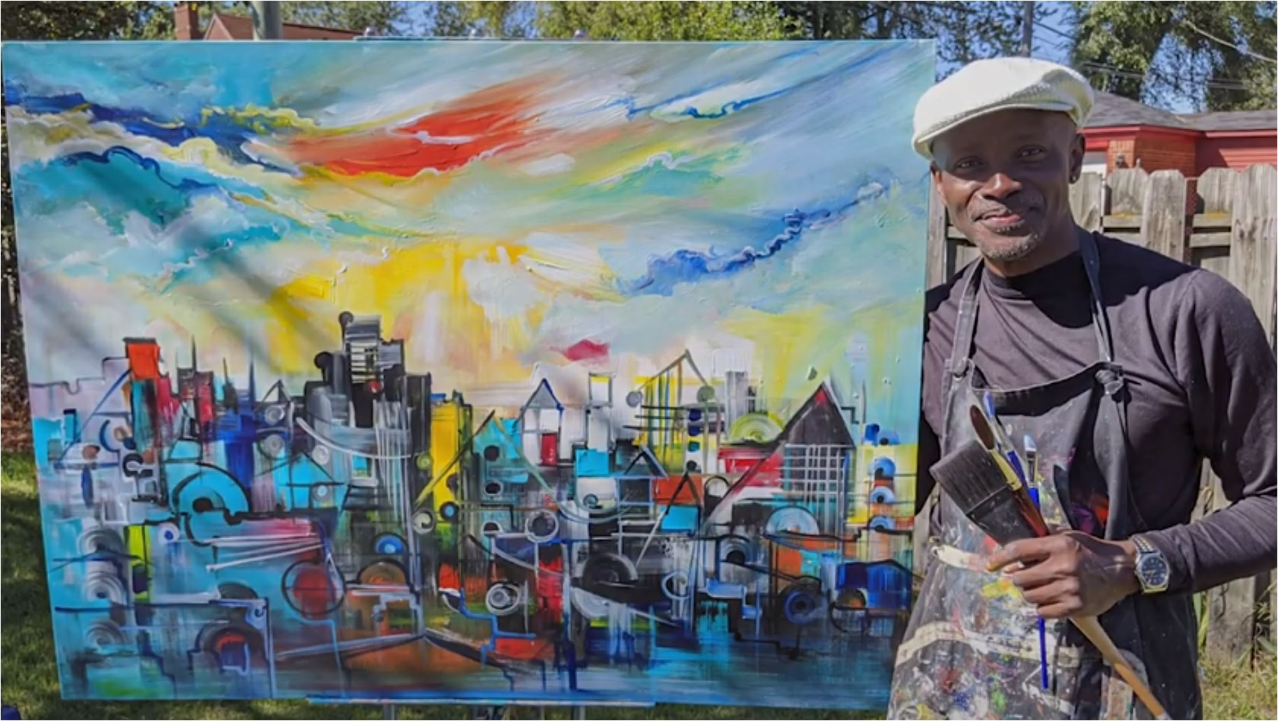 Timothy Orikri stands next to his inspirational painting of Detroit