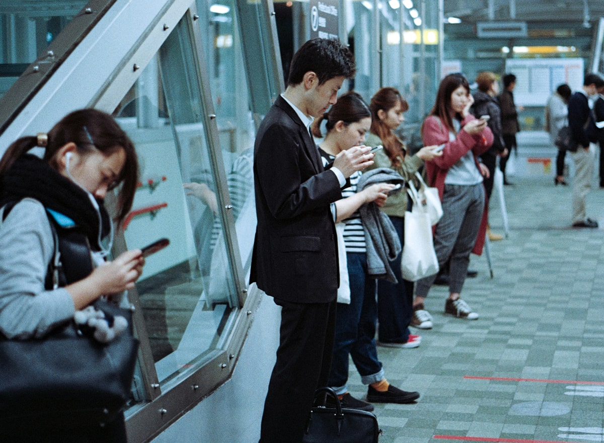train passengers at station, reading their phones while waiting for train to arrive.