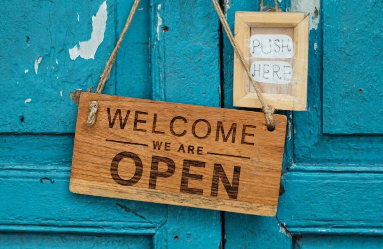 Wooden blue door with brown Welcome, we are open and push here signs on the door.