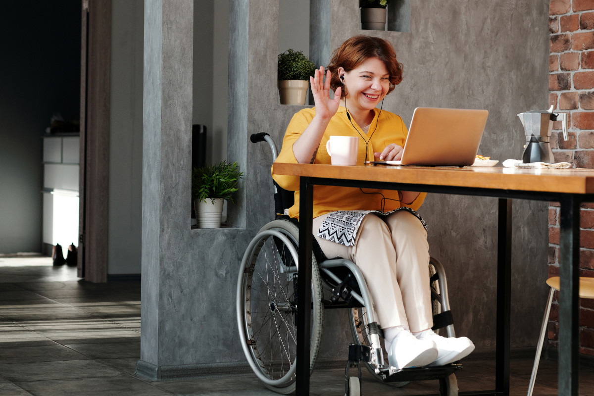 woman in wheelchair at table with open laptop, waving at person on screen.
