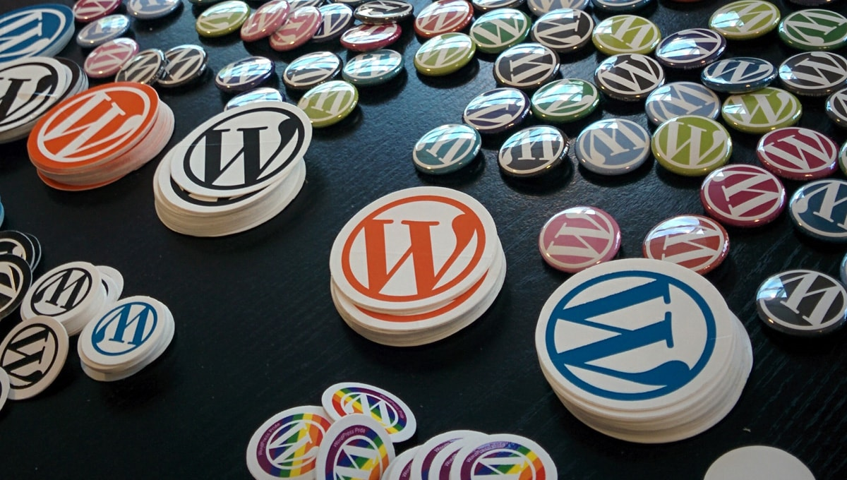 colorful WordPress stickers strewn across a black table