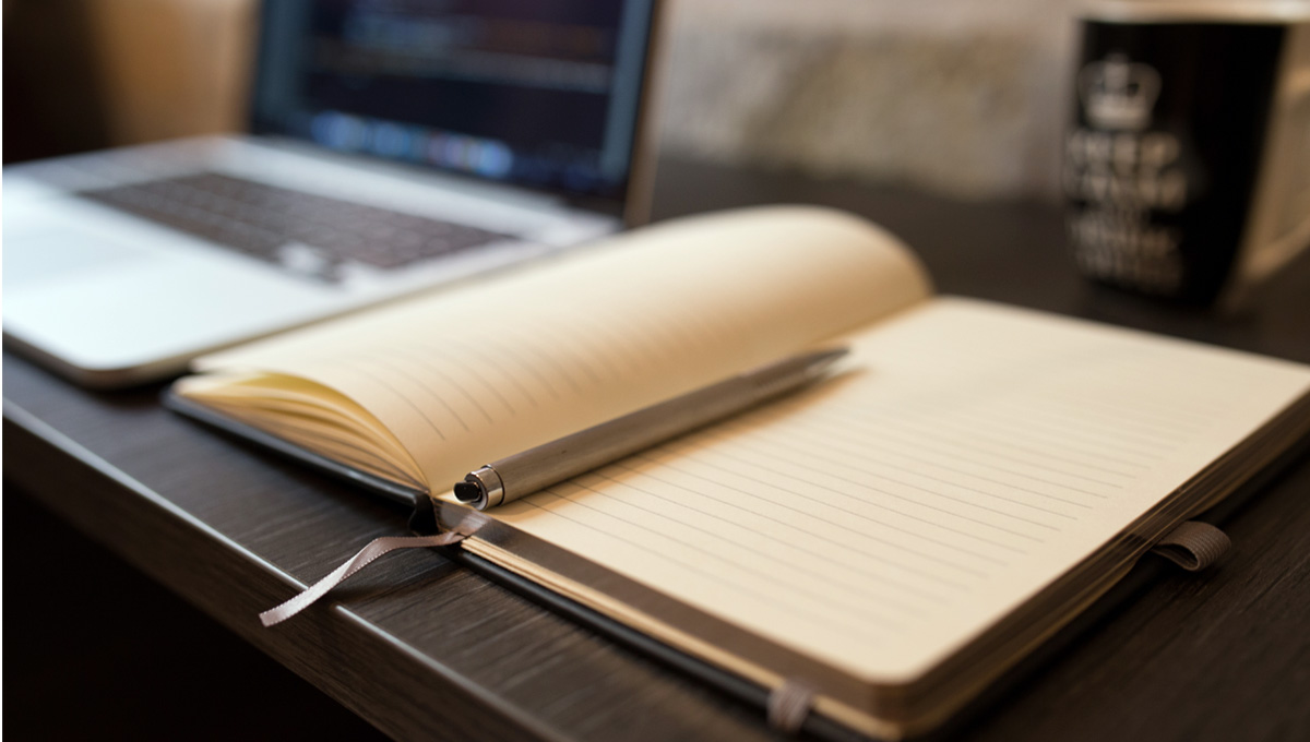 Journal and pen with laptop in background