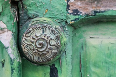 image of weathered door and ornate door knob, Italy, demonstrating home organizer value of attention to detail