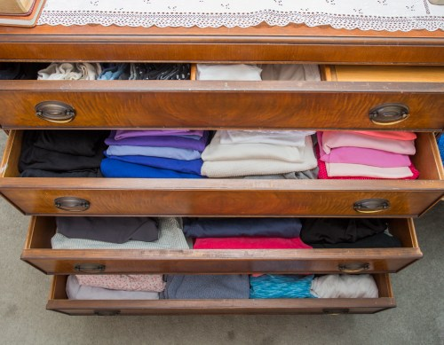 photo of neatly folded clothes in dresser drawers