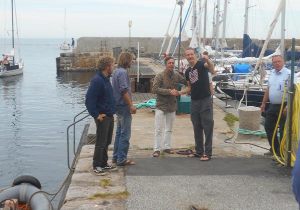 Thomas Svensson [sort t-shirt] fra Gudhjems PROVIANTEN tager imod skibets mandskab. Det er kaptajn Andreas nummer to fra venstre. Foto©JørgenKoefoed.