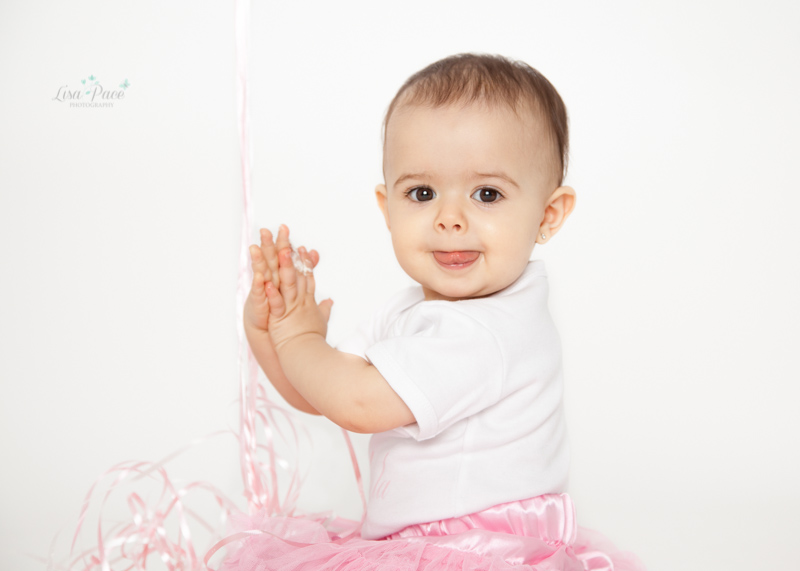 baby girl clapping during cake smash session
