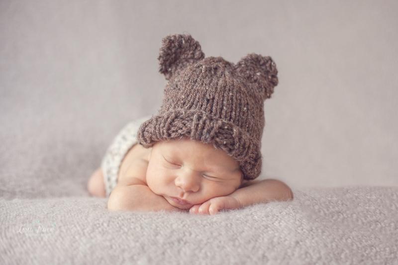 baby asleep on hands wearing bear hat