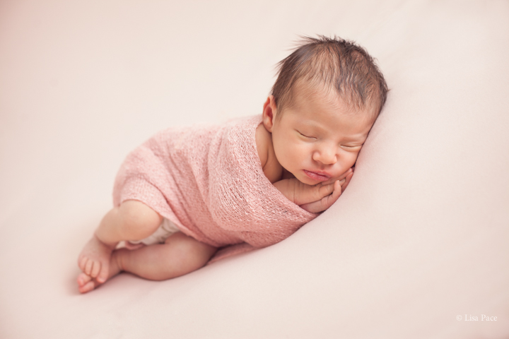 fine art photographer of sleeping baby on her side with hands next to cheeks