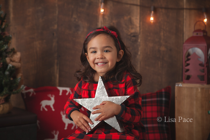 young girl wearing plaid holding silver star