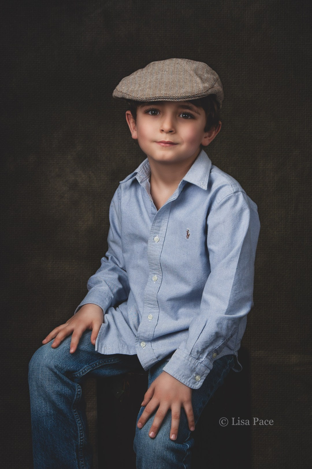 young boy in cap sitting on stool