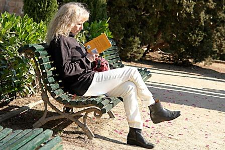 photo of woman reading on a bench