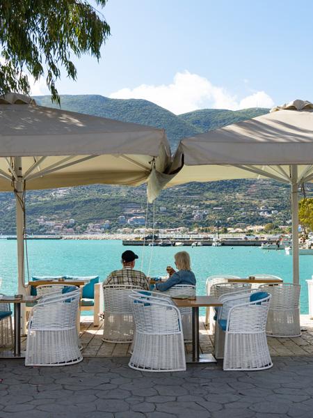 Een ouder echtpaar aan het lunchen bij een restaurantje in het haventje van Vasiliki.