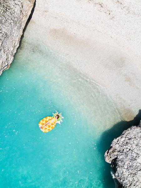 Dronefoto van een vrouw op een ananasluchtbed in de zee op het strand van Kevalikefta