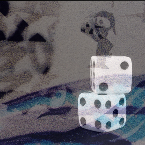 Two dice sit in front of a sandstone-esque petroglyph of an explorer overlooking a foreign landscape. (Photos © FreeImages/Maria Kaloudi and Dora Mitsonia)