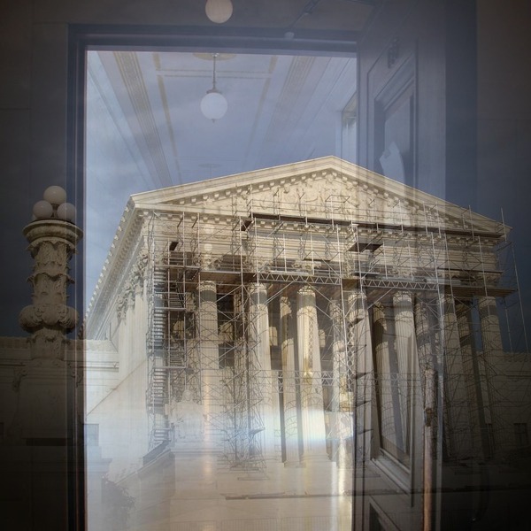 A door and hallway inside the U.S. Supreme Court leads back to the Court's exterior steps and pillars, which are scaffolded for repairs. (Photo © FreeImages/David Lat)