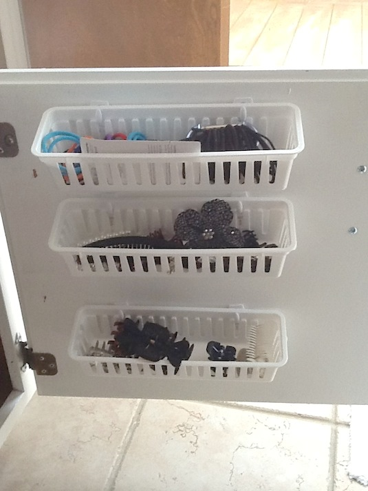 Bathroom storage - Attach dollar store baskets to the vanity door with Velcro or Command hooks to store small items.