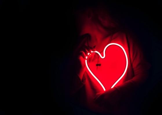 moça no escuro segurando um coração que brilha