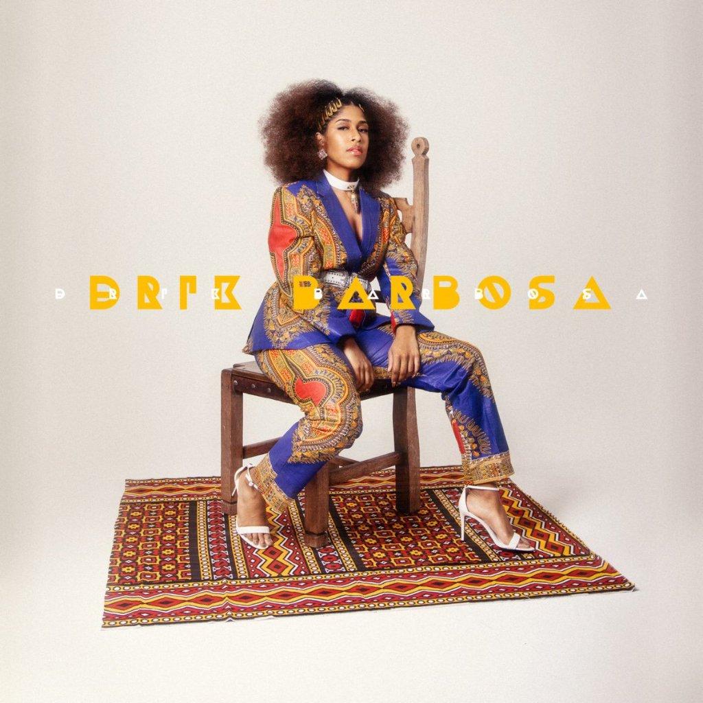 Capa do disco homônimo de Drik Barbosa, que tem a própria sentada numa cadeira de madeira, em cima de um tapete, fundo branco.