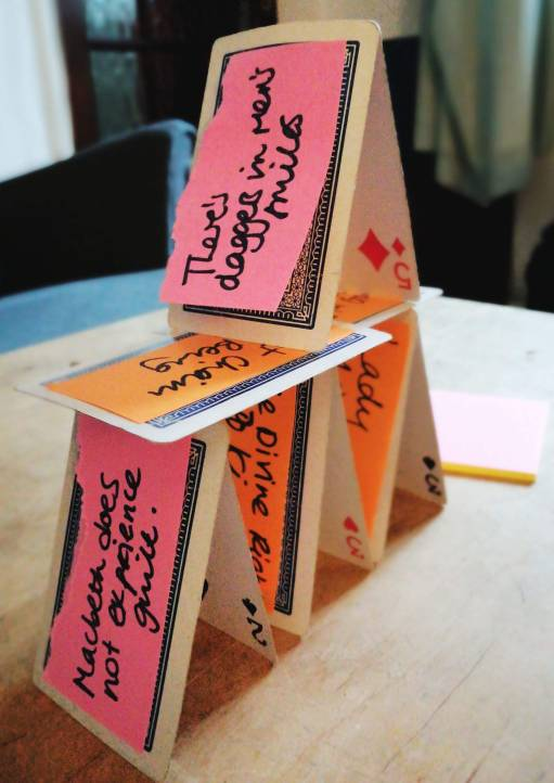 Card Tower with sticky notes on each card. Each sticky note has a different sentence on it.