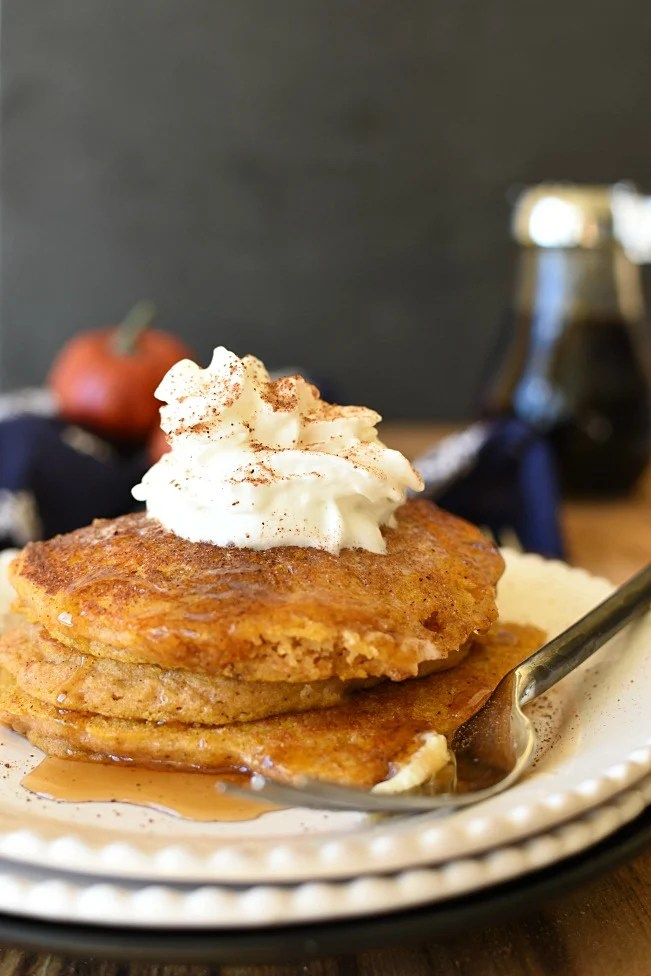 Whole Wheat Pumpkin Pancakes with whipped cream on top