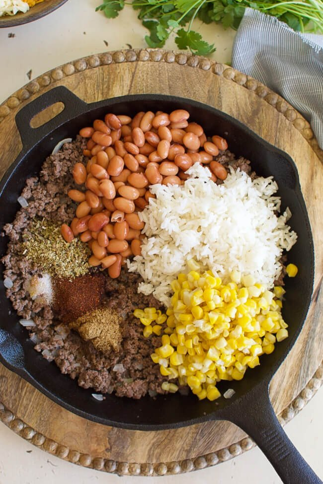 beans, corn, rice, and seasonings over ground beef in a skillet