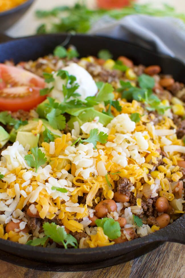 a cast iron skillet with fried hamburger, beans, corn, grated cheese, cilantro and avocados