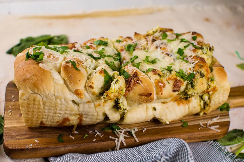 a loaf of cheeesy pull apart bread with chopped parsley on top. Little Dairy on the Prairie